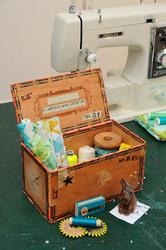 Upcycled cigar box decorated with stamped prints and washi tape repurposed as sewing box containing fabric remnants and reels of thread on work table in front of sewing machine