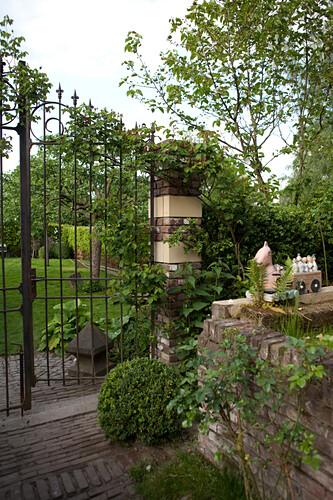 Low brick wall and open, wrought iron garden gate in mature, idyllic garden