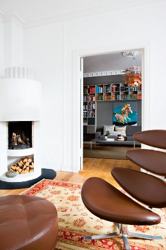 Classic office chair with brown leather cover and matching footstool; white corner fireplace in background next to open double doors with view into library