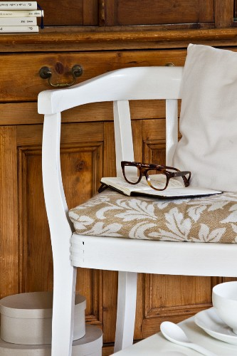 Stripped wooden cabinet behind white-painted armchair; notebook and glasses on patterned seat cushions