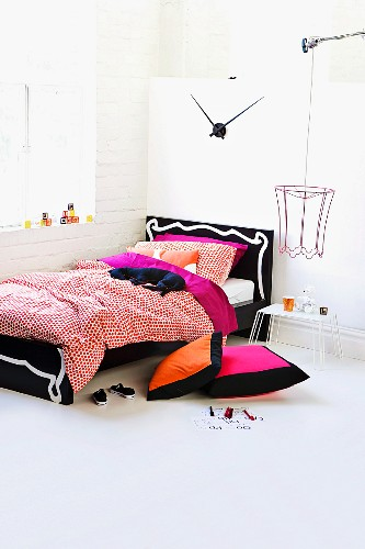 Colourful bed linen and soft toy on wooden bed with ornate headboard and wire lampshade in teenager's bedroom