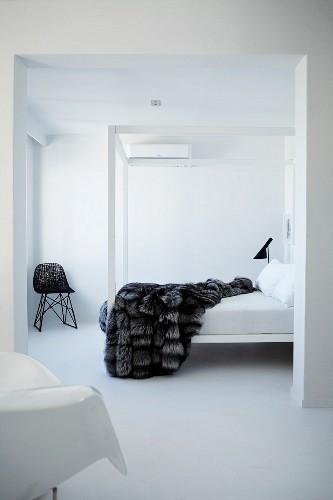 White, minimalist bedroom with fur blanket on canopied bed; Bauhaus wicker chair in corner