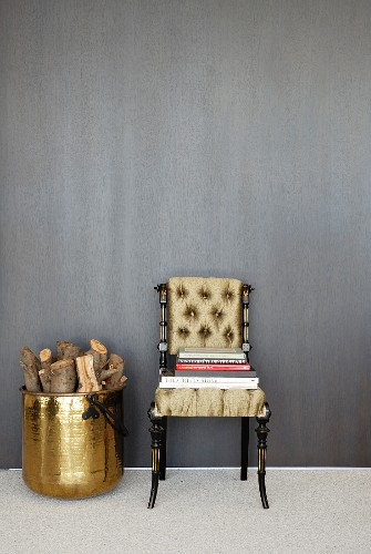 Neo-antique chair with upholstered seat and back with books stacked on seat next to brass pot of logs against grey wall