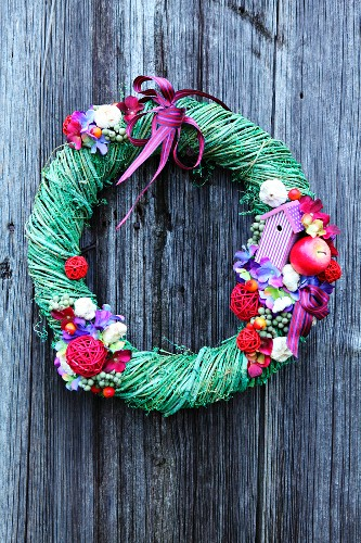 Willow wreath with multicoloured flowers and fruits on wooden wall