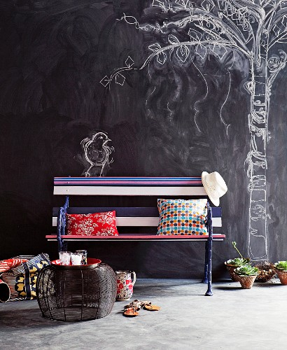 Romantic park atmosphere in living room with colourfully painted garden bench and tree and bird drawn on chalkboard wall