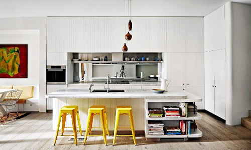 White fitted kitchen with mirrored splash guard, kitchen island with marble worktop and yellow retro bar stools