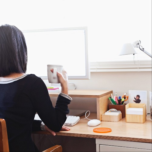 Woman sitting in front of computer monitor with mug of coffee