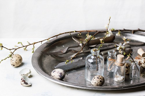 Quail eggs, vintage tableware and vials with blossom branches on old metal tray