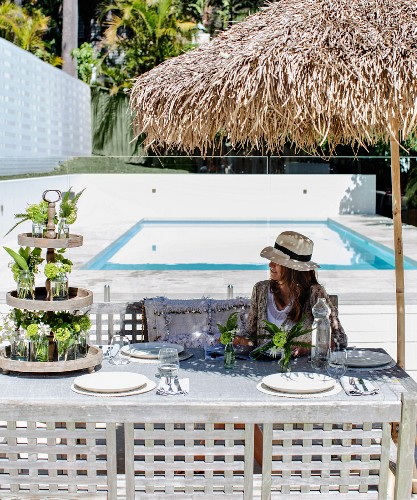 Woman sitting at festively set table below parasol next to pool