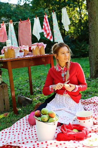 Young woman sitting on picnic blanket peeling apple in front of preserving jars on table and washing line