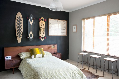 Bed with wooden headboard below painted skateboards on black-painted wall; three stools below window with closed louver blinds to one side