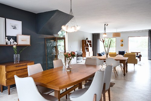 Dining area with white, upholstered chairs around wooden table, chest of drawers and display case against black-painted wall; classic shell chairs around rustic table in background in open-plan interior