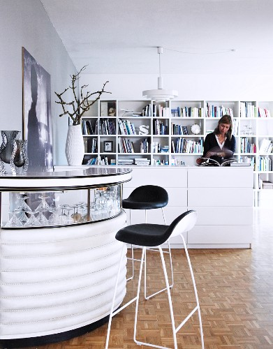 Bar stools at semicircular bar with glass top, woman in background next to half-height, white chest of drawers and bookcase