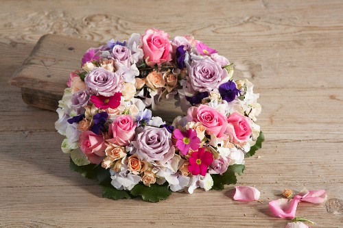 Wreath of flowers of various colours on wooden surface