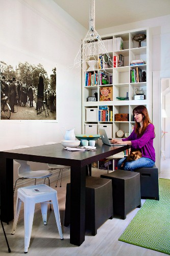 Woman working on laptop on dark wooden table, stools of various styles and bookcase in background