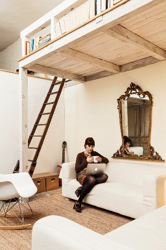 Young woman with laptop sitting on ecru sofa below white-painted wooden mezzanine accessed by wooden ladder in open-plan interior with vintage character