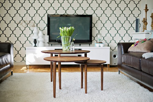 Nest of 50s tables, black leather sofas and modern media centre against wallpaper with stylised azulejo pattern