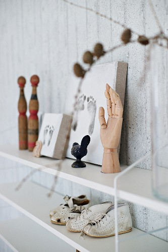 Memorabilia such as framed footprints and booties on shelves on exposed concrete wall