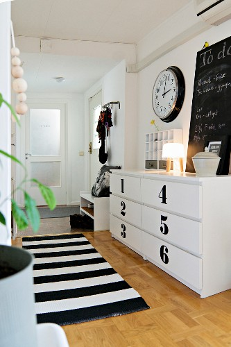 Chest of drawers with numbered fronts below station clock and to-do list on blackboard in entrance hall