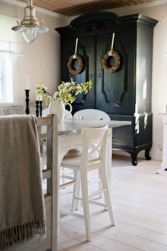 Corner of dining set with white kitchen chairs in front of black farmhouse cupboard decorated with wreaths