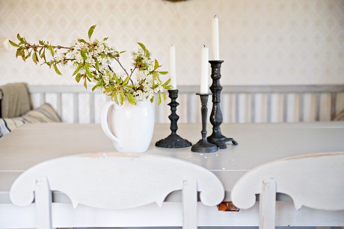 Branches of leaves in china jug and candlesticks on table behind curved backrests of kitchen chairs
