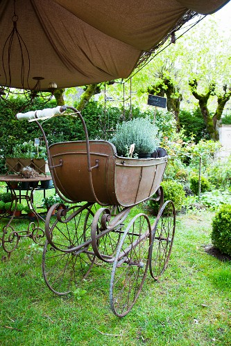 A sales exhibitions under a pergola in the garden of a French country house - plant pots with price labels in a an antique pram