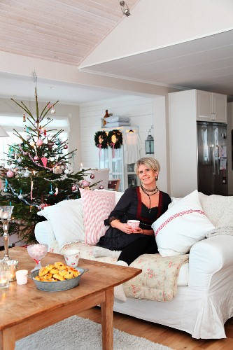 Woman sitting on white sofa next to decorated Christmas tree in rustic living room