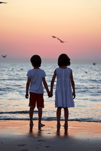 Little boy and girl hand in hand on beach at sunset