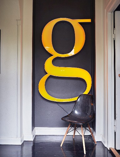Charles Eames shell chair below huge decorative letter G on dark-painted wall