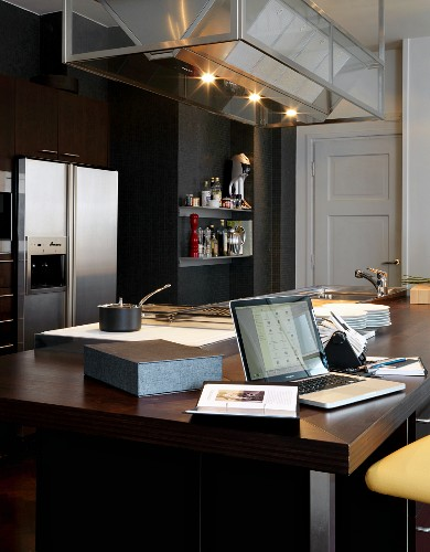 Modern, dark wood kitchen doubles as office space