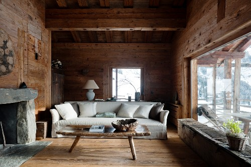 Pale, loose-covered sofa with scatter cushions behind rustic wooden coffee table in living room of cabin with panoramic window to one side