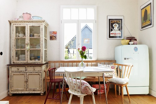 Dining area in rustic ambiance with chairs and bench below window between dresser with glass-fronted top cabinet and fridge