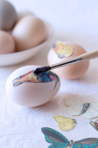 Decorating eggs using decoupage - glueing bird and butterfly motifs to eggs