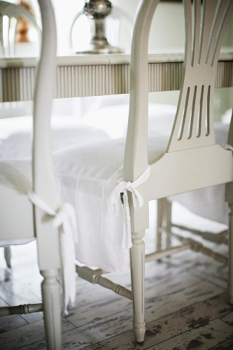 White-painted wooden chairs seat covers over seat cushions