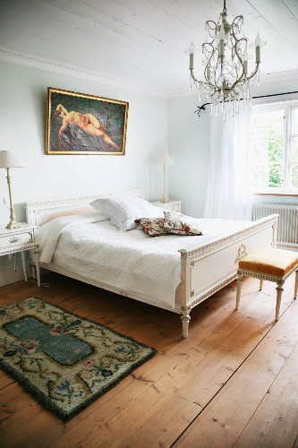 Simple bedroom with Regency-style double bed and bedside table painted white below chandelier wit glass pendants