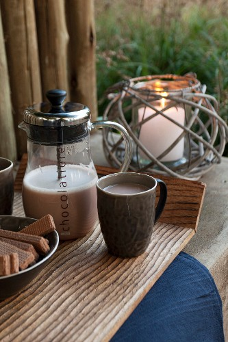 Coffee and wafers on tray next to candle lantern on surface