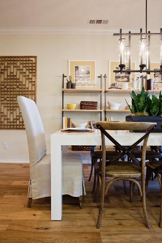 Wohnraum mit Stühlen am Esstisch & Regalen im Hintergrund