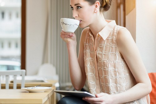 Young businesswoman in cafe drinking coffee and using digital tablet