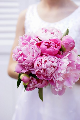 Girl holding bouquet of pink peonies
