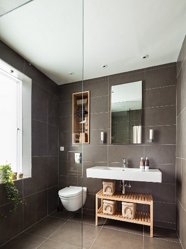 Grey Tiled Bathroom With Shelves In