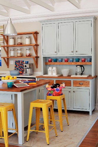 Yellow vintage bar stools at counter in pastel grey Shaker-style kitchen