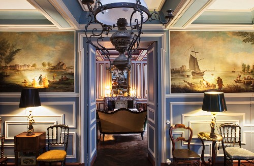 Dining room with antique paintings on blue and white wood panelling and antique glass lamp; view into adjoining parlour