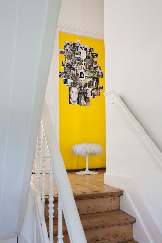 Staircase in old, Scandinavian house with view of photo collage on yellow-painted wall