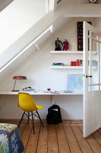 Yellow classic chair in workspace with floating desk and shelves under sloping ceiling