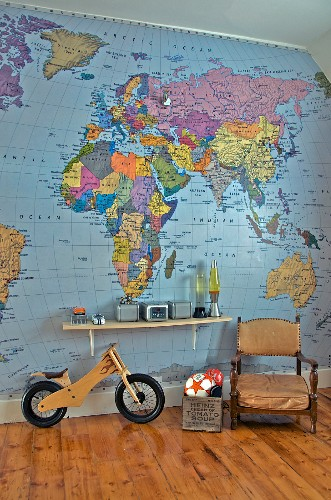 Antique armchair next to toy box and balance bike below bracket shelf on wall papered with map of world