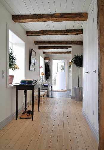 Hallway in renovated wooden house with white wood cladding and ceiling beams