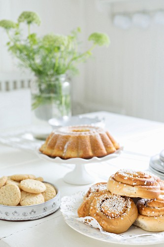 Coiled pastries, biscuits and bundt cake on table set for afternoon coffee with white tablecloth
