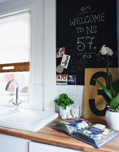 Detail of kitchen counter with open book on wooden worksurface and writing on blackboard next to window