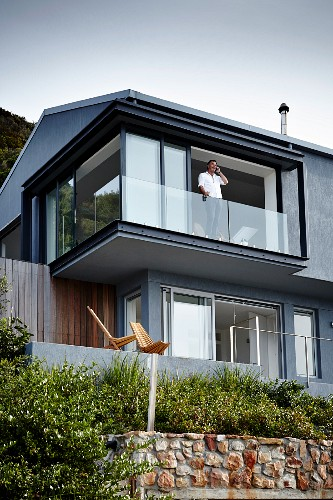 Contemporary house with grey-painted facade; man standing behind glass balustrade of open terrace windows of upper storey