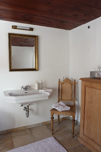 Sink below gilt-framed mirror next to antique chair in renovated bathroom